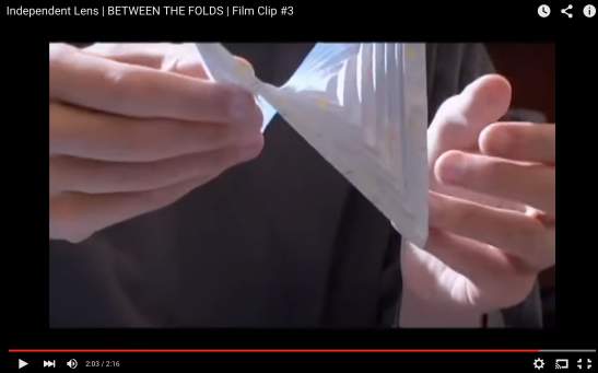 Erik Demaine holding a folded paper Warped Square